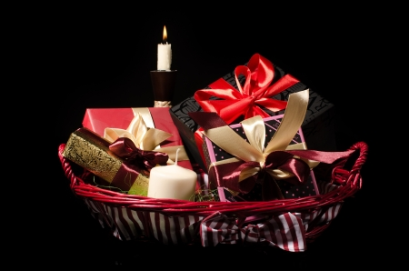 Gifts basket and candle against black background photo