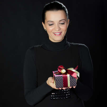 Beautiful woman presenting a gold gift box against black background Stock Photo - 17866258