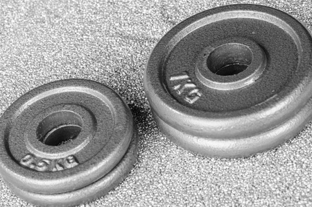 discs: Dumbbell weights over a shiny grey sand Stock Photo