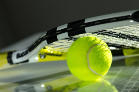 Tennis ball  and a racket on it against a dark background photo
