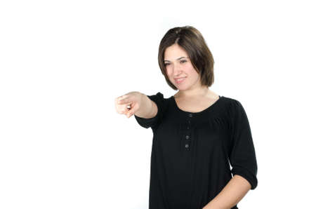 Portrait of young woman pointing in front of her against white background