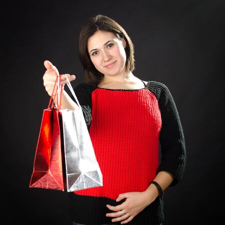 Portrait of young woman with gift bags against black background Stock Photo - 17866292