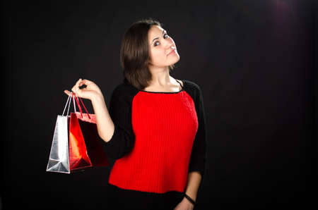 Portrait of young woman with gift bags against black background Stock Photo - 17866306