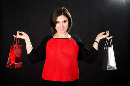 Portrait of young woman with gift bags against black background Stock Photo - 17866329