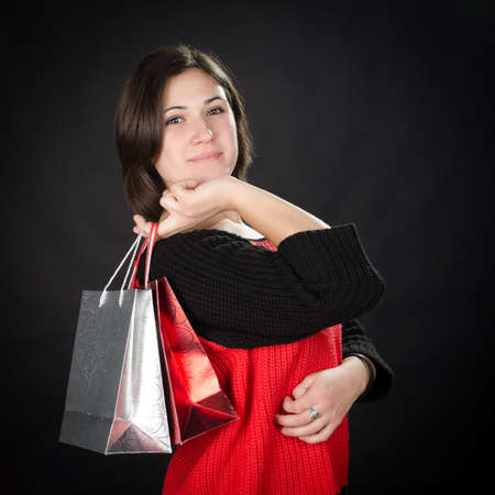Portrait of young woman with gift bags against black background Stock Photo - 17866295