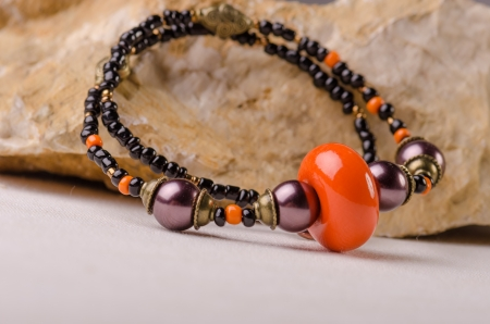 Handmade jewellery and a stone on white background