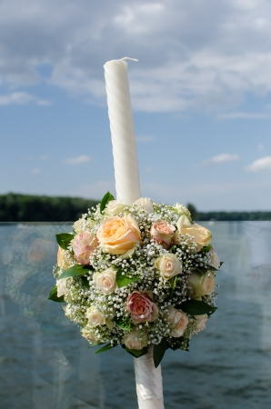 Weeding candle with floral arrangement against lake view
