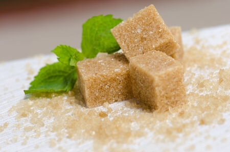 sucrose: Brown sugar cubes and mint on white surface  Stock Photo