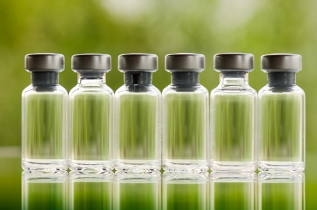 Vials of medicine against green  background