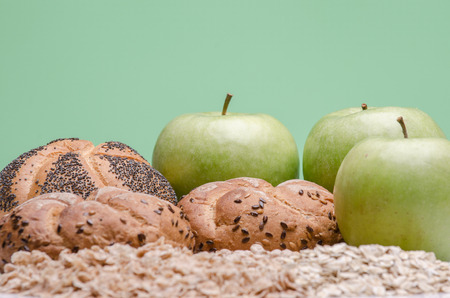 Bead, oat cereals and green apples against green background