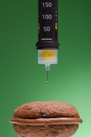 Insulin pen and cookie against green background