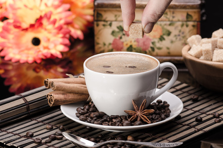 Brown sugar on a cup of coffee  with anise and cinnamon against orange flower background  photo