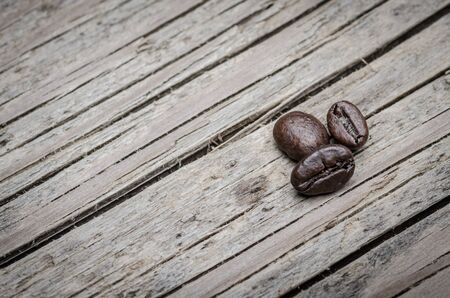 Coffee beans presented on wooden surface photo