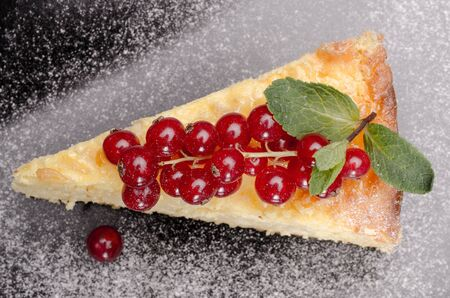 Slice of pudding cheese and red currant on a black plate top view Stock Photo
