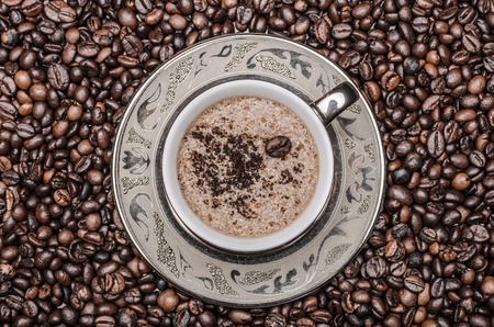 Hot cup of coffee with foam  on coffee beans    Kho ảnh