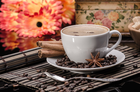 Cup of coffee  with anise and cinnamon against orange flower background   photo