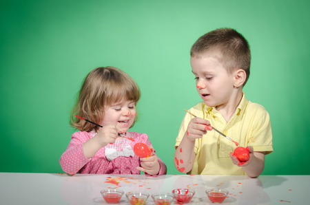 Happy children   painting Easter eggs against green background Stock Photo