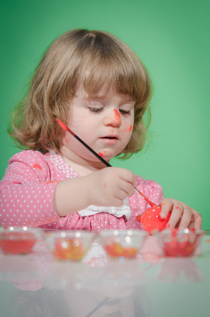 Beautiful baby girl painting Easter eggs against green background