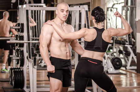 Strong man and a woman posing in a gym photo