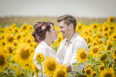 Beautiful loving couple in a sunflower field under the summer sun photo