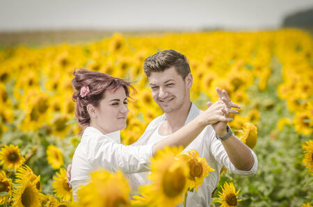 Beautiful couple  dancing in a sunflower field under the summer sun photo