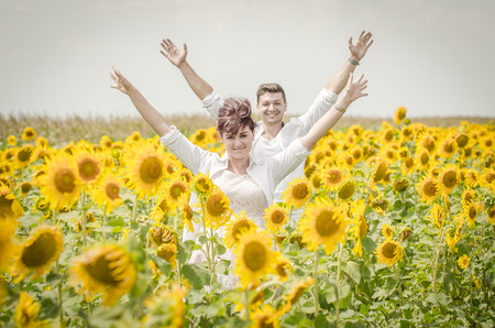 Beautiful couple raising arms in a sunflower field photo