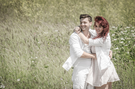Loving young couple sitting in a wheat field under the summer sun photo