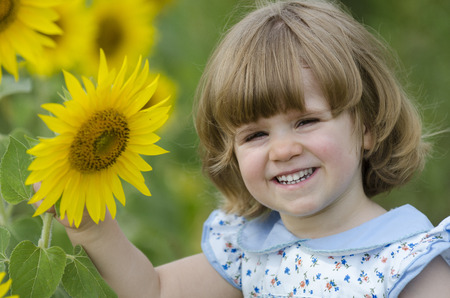 Little girl playing around in a sunflower field photo