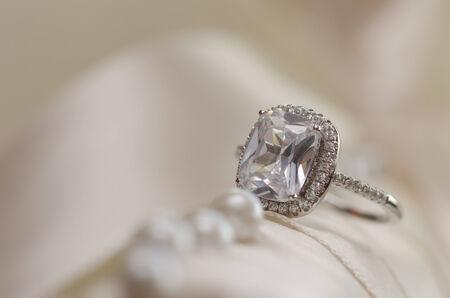 anillo de compromiso: Anillo de bodas de diamante contra el fondo borroso de luz