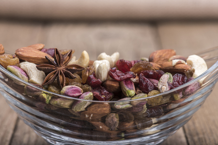 Pistachio and nuts closeup in a glass bowl wooden background