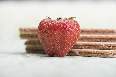 Strawberry and wafers against a light green background