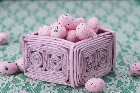 paper basket: Pink Easter eggs in a pink recycled paper basket against a green and white lacy background