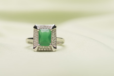 light green background: Green stone ring against a light green background