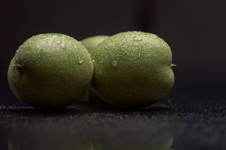 copra: Green nuts with water drops on a black reflective surface