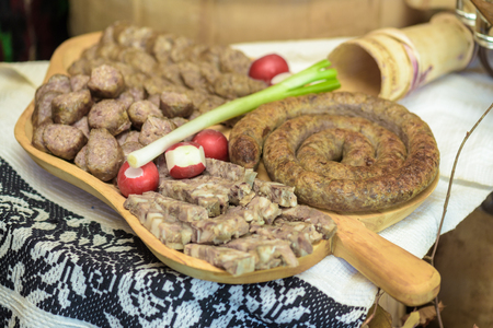 greaves: Appetizers with greaves, sausages, specialty pork, radishes and green onion on wooden  plate