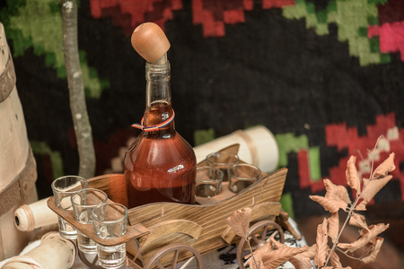brandy: Homemade brandy in a small bottle and small glasses against handmade vintage background Stock Photo