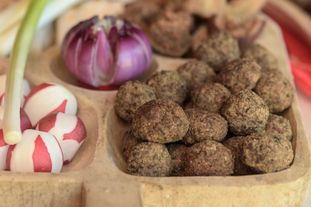 greaves: Appetizers with meatballs. radishes and red onions on wooden plate close up