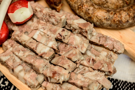specialty: Appetizers with   specialty pork and radishes on a wooden plate close up Stock Photo