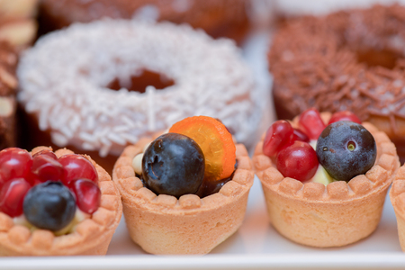 Mini tarts with vanilla cream, blueberries and pomegranate for candy bar Stock Photo