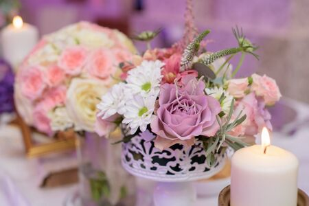 Arrangement for table with flowers and candles for christening party close up Stock Photo