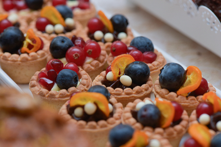 Mini tarts with vanilla cream, blueberries, redcurrants and pomegranate for candy bar Stock Photo