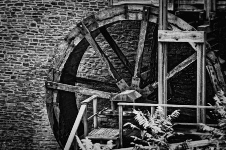 Old water mill wheel in front of stone wall. Black and white. Stock Photo