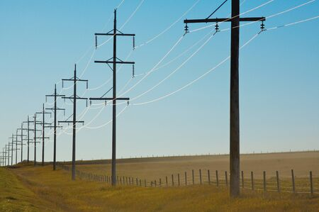 utility pole: Sunlight reflecting on electrical power lines Stock Photo