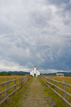 Small white country church with fence and stormy clouds Stock Photo