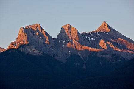 Morning sunlight on the Three Sisters mountain group in the Rocky Mountains of Canada