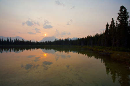 assiniboine: Sun setting over distant mountains and reflected in Buller Lake Rocky Mountains of Canada Stock Photo