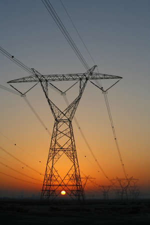 hydro: Sun setting behind electrical power pylons