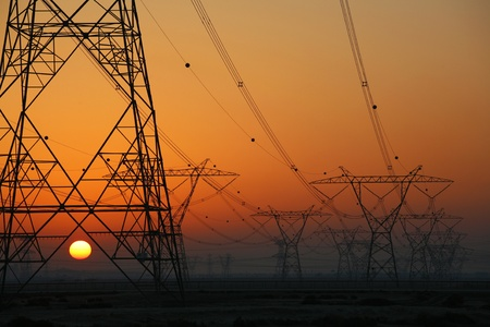 Puesta de sol detr�s de torres de energ�a el�ctrica Foto de archivo - 11651992