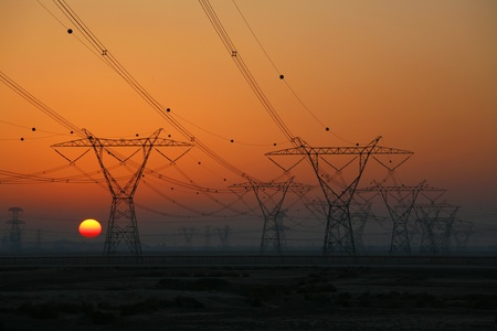 Sun setting behind electrical power pylons