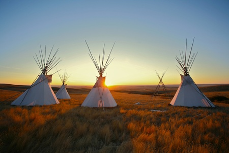 native american indian: Tipis on the prairie at sunrise Stock Photo